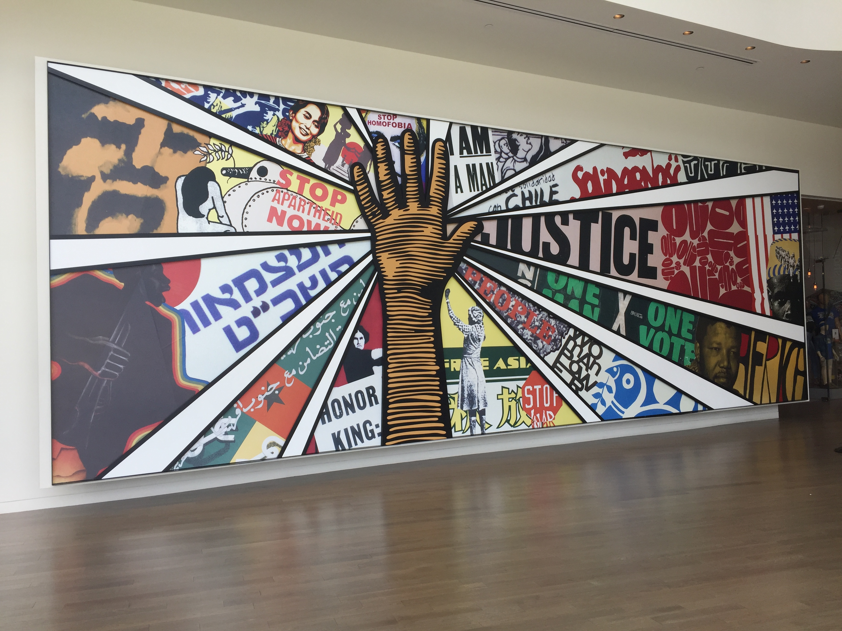 """Photo is of a painting that has a hand in the middle and segments of colorful images meeting that hand in the middle. One of the segments says """"Justice."""" Another says """"Stop Apartheid Now."""""""